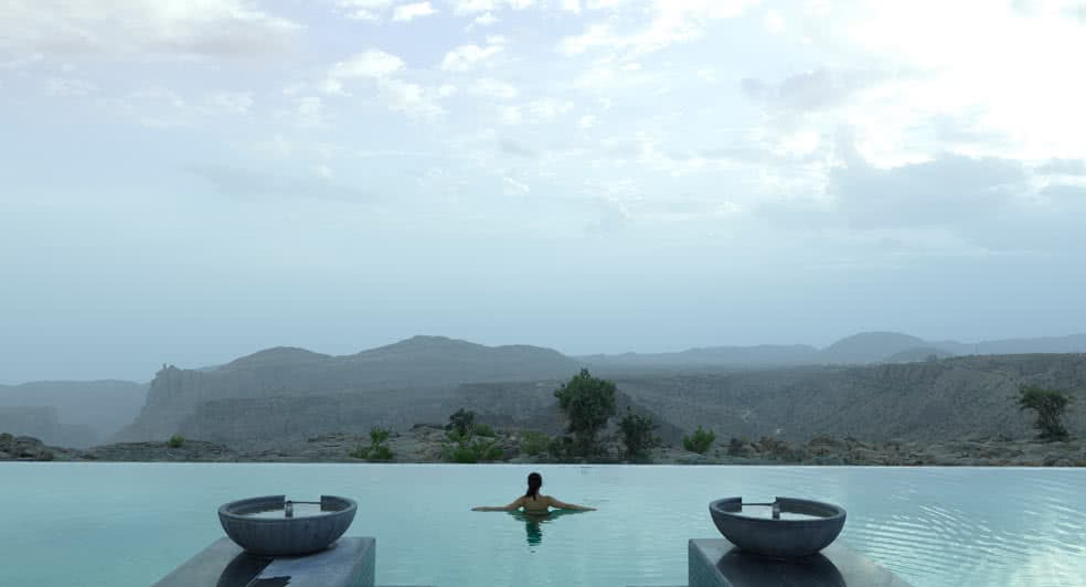 Swimming Pool with Panoramic View of Green Mountains in Oman